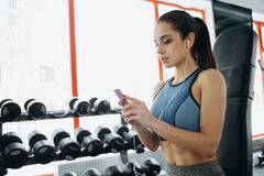 Portrait of young and attractive woman in blue top and with ponytail standing in gym, using her mobile phone and smiling Stock Photography