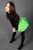 Portrait of a young attractive woman in a bright green skirt. Over grey background Stock Images