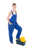 Portrait of young attractive woman builder in blue workwear with Royalty Free Stock Photo