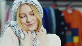Portrait of a young attractive woman in a clothing store. She tries on a hat, looking up and smiling at the camera stock video