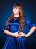 Portrait of a young attractive woman in a dark blue evening dres. S over black background Stock Photos