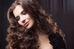 Portrait of a young attractive woman with gorgeous curly hair. Attractive brunette. Close up royalty free stock image