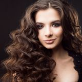 Portrait of a young attractive woman with gorgeous curly hair. Attractive brunette stock image