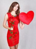 Portrait of a young attractive woman with a heart-shaped pillow Royalty Free Stock Photo