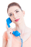 Portrait of young attractive woman holding telephone receiver Stock Photo