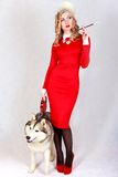 Portrait of a young attractive woman with a husky dog. Over grey background Royalty Free Stock Images