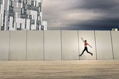 Portrait of young and attractive woman jumping next to the wall. Portrait of young and attractive woman jumping next to the wall in urban park, Barcelona, Spain Stock Photo
