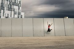 Portrait of young and attractive woman jumping next to the wall in urban park. Portrait of young and attractive woman jumping next to the wall in urban park Royalty Free Stock Images