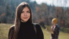 Portrait young attractive woman looking into the camera in the mountains. Tourist with a map in the background stock video