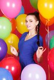 Portrait of a young attractive woman among many bright balloons Stock Photography