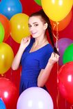 Portrait of a young attractive woman among many bright balloons Stock Photo