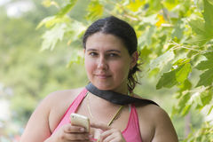 Portrait of young attractive woman with a mobile phone at summer green park Royalty Free Stock Photography