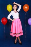 Portrait of a young attractive woman near many bright balloons Stock Photography