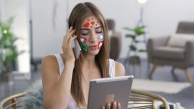 Portrait of young attractive woman with painted social media icons on her face talking by phone while holding the tablet. In hands. Addiction to gadgets stock footage