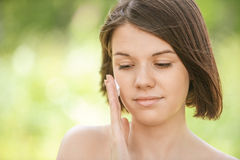 Portrait of young attractive woman putting cream on her face Royalty Free Stock Images