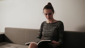 Portrait of a young attractive woman reading a magazine while sitting on the couch in her living room. Leisure time stock video footage