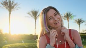 Portrait of young attractive woman in red swimsuit boby smiling cheerful wearing white headphones. Sun and palmas stock video footage