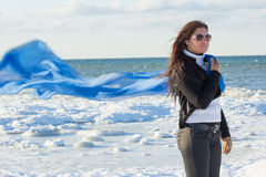 Portrait of young woman with scarf on winter beach Stock Photos