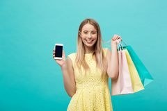 Portrait young attractive woman with shopping bags shows the phone`s screen directly to the camera. Isolated on blue. Background royalty free stock images