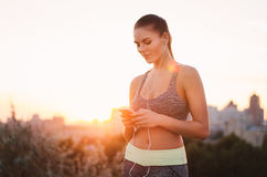 Portrait of a young attractive woman in sportswear, listening to royalty free stock photography