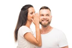 portrait of young attractive woman whispering to her boyfriends ear, stock photos