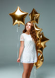 Portrait young attractive woman in white dress, holding bunch of Royalty Free Stock Images