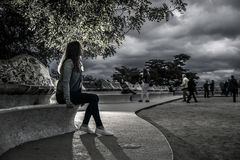 Portrait of young and attractive woman, who is sitting on the bench. Stock Image