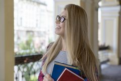 Portrait of young attractive women girl student in glasses with. Portrait of young attractive woman girl student in glasses with long blond hair and books with Stock Photo