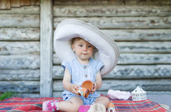 Portrait of young baby girl in big hat sitting in front of old retro wooden house Stock Photo