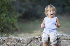 Portrait of young baby girl making faces. Outdoor portrait of young baby girl making faces Royalty Free Stock Photography