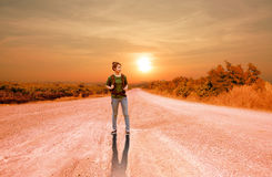 Portrait of young backpacker woman on country road Stock Photo