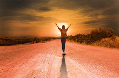 Portrait of young backpacker woman on country road Royalty Free Stock Images