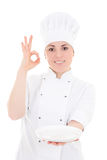 Portrait of young baker woman in uniform with empty plate showin Stock Photos
