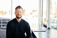 Portrait of young bearded business man in front of his working place in modern office Royalty Free Stock Photo