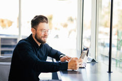 Portrait of young bearded business man use phone at working place in modern office Stock Image