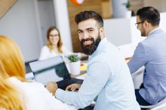 Portrait of  young bearded  businessman and his team. Portrait of  young bearded  businessman who is turned , team sitting at  table in office and  brainstorming Stock Photography