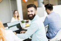 Portrait of  young bearded  businessman and his team. Portrait of  young bearded  businessman who is turned , team sitting at  table in office and  brainstorming royalty free stock photography