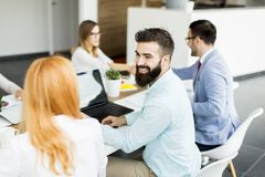 Portrait of  young bearded  businessman and his team. Portrait of  young bearded  businessman who is turned , team sitting at  table in office and  brainstorming stock photos