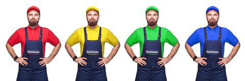 Portrait of young bearded confident with working clothes, four different color t-shirt and cap standing and holding hands on waist. Smiling. indoor studio shot stock photos