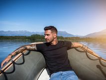 Alluring tattooed man in boat. Portrait of young bearded handsome man with tattooed body looking sexually at camera sailing in boat Stock Photos