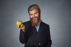 Business man holds one green apple and smiles stock images