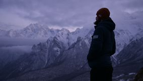 Portrait of a young bearded male traveler at dusk in the mountains. Stand seriously thinking and looking around. Warmly. Dressed guy on the background of snowy stock video