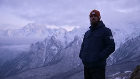 Portrait of a young bearded male traveler at dusk in the mountains. Stand seriously thinking and looking around. Warmly. Dressed guy on the background of snowy stock video footage