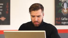 Portrait of a young bearded man businessman in a coffee shop, he works on laptop. Successful serious man in a black sweater working on a laptop with documents in stock video footage