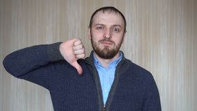 Portrait of young bearded man gesture thumbs down indoors.  stock footage