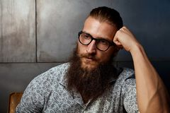 Portrait of young smart bearded man in glasses. Portrait of young bearded man in glasses, looking away with serious expression Royalty Free Stock Photos
