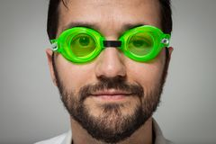 Portrait of a young bearded man with swimming glasses. Portrait of a young bearded man with green swimming glasses on grey background Stock Images