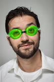 Portrait of a young bearded man with swimming glasses. Portrait of a young bearded man with green swimming glasses on grey background Royalty Free Stock Photo