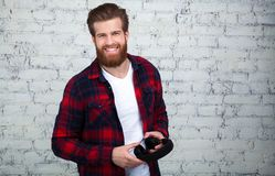 Portrait of a young bearded man with headphones in his hands on brick wall stock image