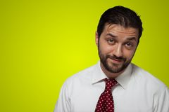 Portrait of a young bearded man. With red tie on yellow background Royalty Free Stock Photography